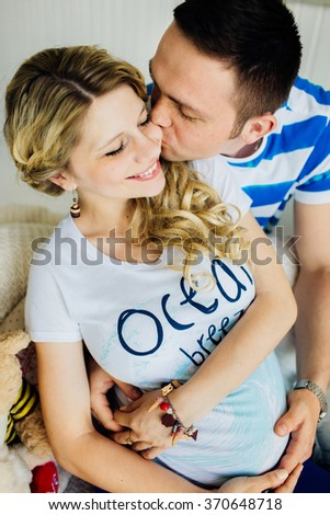 Portrait of expecting couple laughing happily, embracing baby in belly together. Couple dressed in blue and white colors. - stock photo