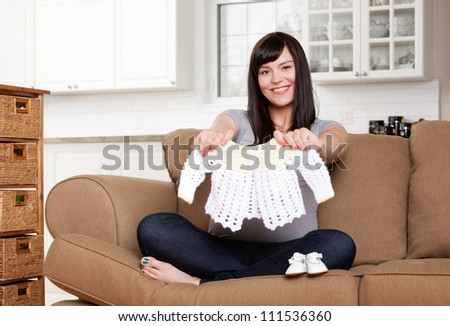 Portrait of expecting mother holding up knitted sweater - stock photo