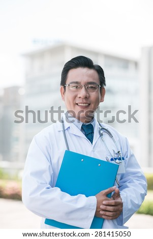 Portrait of experienced Asian practitioner with a folder