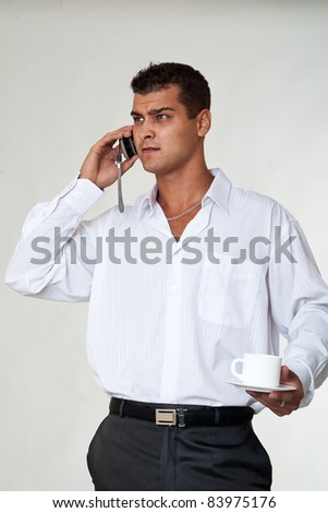Portrait of expression business man calls phone and drinking coffee - stock photo