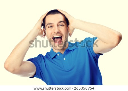 Portrait of expressive surprised or shocked happy young handsome man in blue casual t-shirt clothing - stock photo
