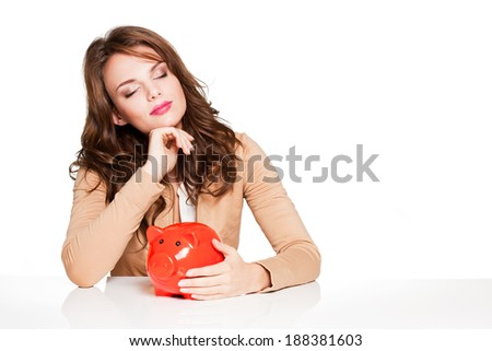 Portrait of expressive young brunette woman with her piggy bank.