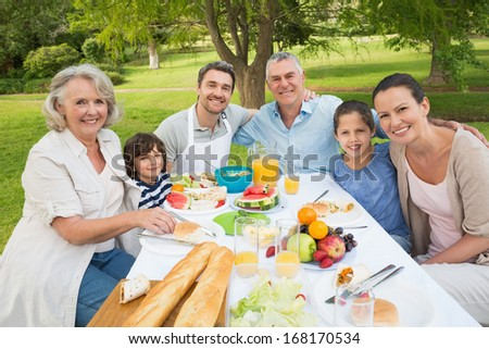 Portrait of extended family dining at outdoor table - stock photo