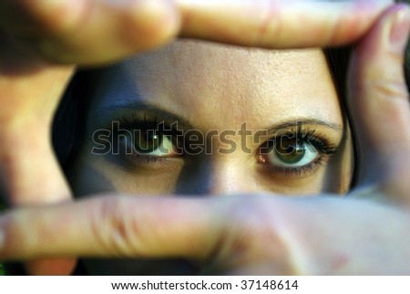 Portrait of eyes looking through fingers frame