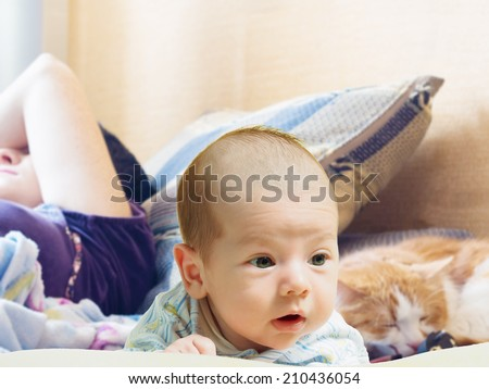 Portrait of face funny caucasian newborn toddler baby boy with sleeping mother and red cat - stock photo