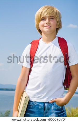 Portrait of fair-haired boy looking at camera outdoors