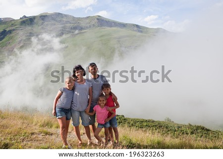 Portrait of family at cloudy Pyrenees mountain background. Andorra