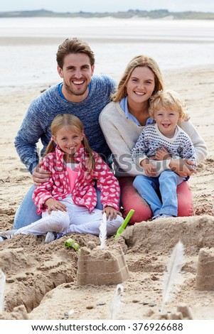 Portrait Of Family Building Sandcastles On Beach Together - stock photo