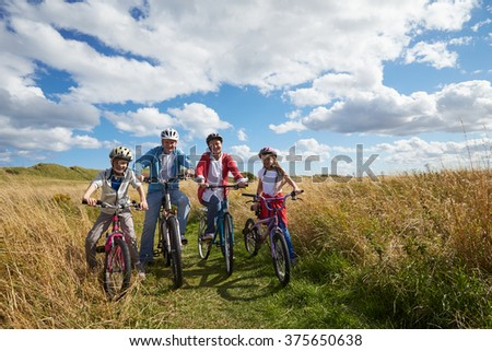 Portrait Of Family Cycling Through Countryside Together - stock photo