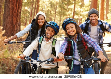 Portrait Of Family Cycling Through Fall Woodland - stock photo