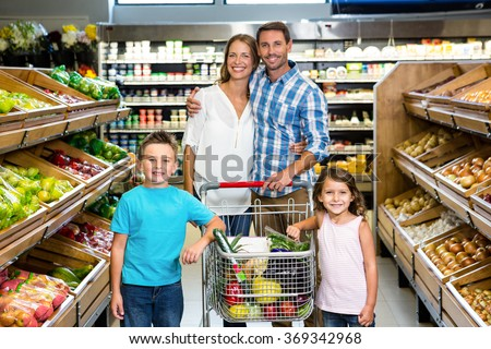 Portrait of family doing shopping in grocery store - stock photo