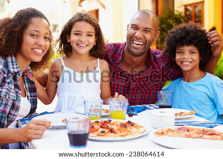 Portrait Of Family Eating Meal At Outdoor Restaurant - stock photo