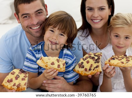 Portrait of family eating pizza on sofa at home