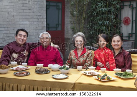 Portrait of family enjoying Chinese meal in traditional Chinese clothing - stock photo