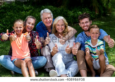 Portrait of family gesturing thumbs up while relaxing at yard - stock photo
