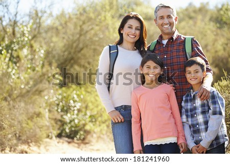 Portrait Of Family Hiking In Countryside Wearing Backpacks - stock photo