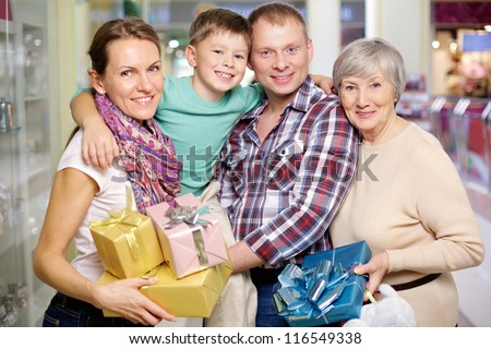 Portrait of family holding giftboxes in the shop - stock photo