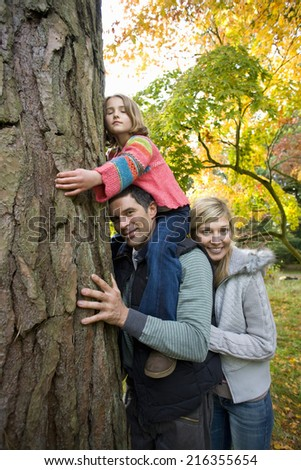 Portrait of family hugging tree trunk - stock photo