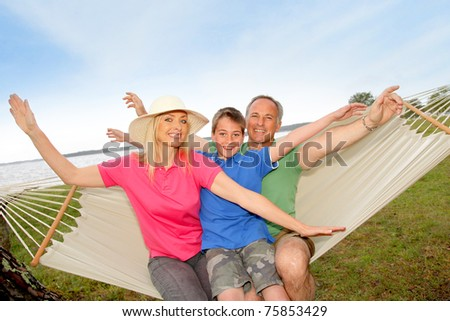 Portrait of family in a hammock - stock photo