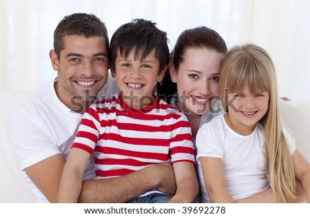 Portrait of family in living-room sitting on sofa together - stock photo