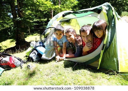 Portrait of family laying in camp tent - stock photo