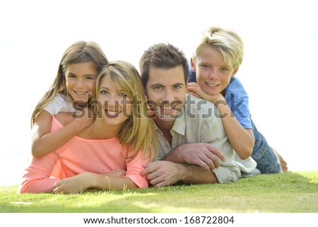 Portrait of family laying on the grass - stock photo
