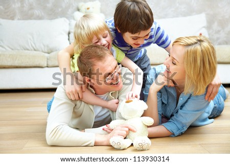 Portrait of family lying on floor living room and smiling to camera - stock photo