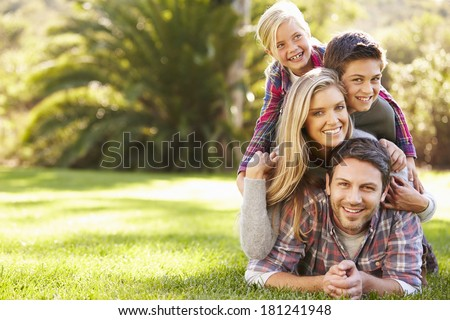 Portrait Of Family Lying On Grass In Countryside - stock photo