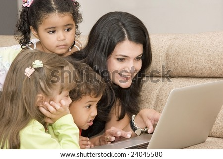 Portrait of family, mom and children enjoying indoor with a laptop