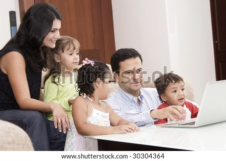Portrait of family, mom, dad and their children enjoying indoor with a laptop