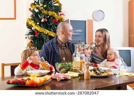 Portrait of family of four over celebratory table at home interior