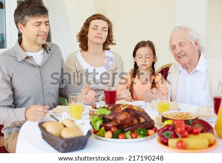 Portrait of family of four praying at festive table on Thanksgiving day