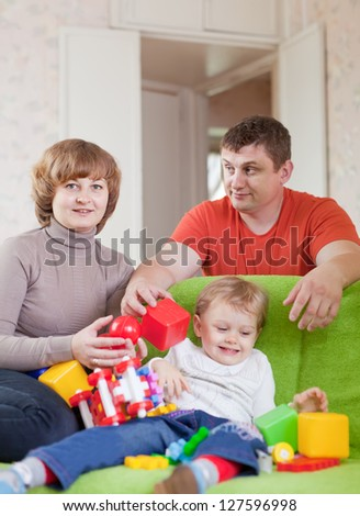 Portrait of family of three in home