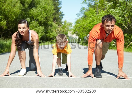 Portrait of family of three standing on start before running - stock photo