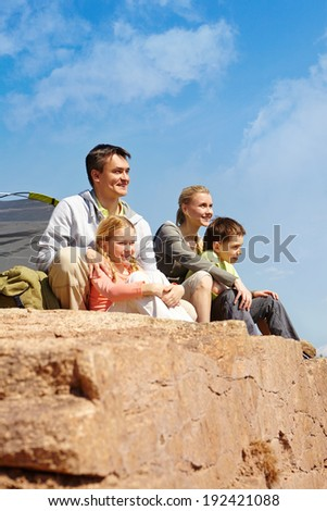 Portrait of family of travelers sitting on rocky cliff - stock photo