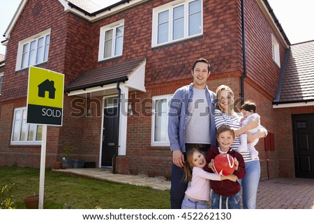 Portrait Of Family Outside New Home With Sold Sign - stock photo