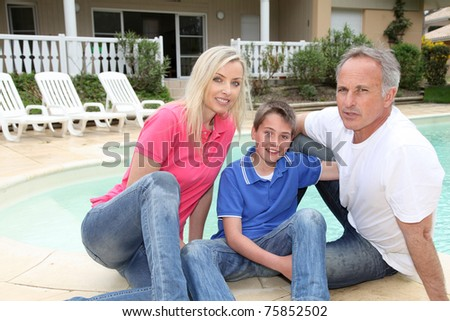 Portrait of family sitting by pool side - stock photo