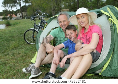 Portrait of family sitting in camping tent - stock photo