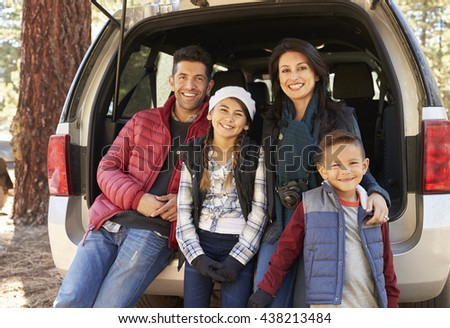 Portrait of family sitting in open back of car before a hike - stock photo