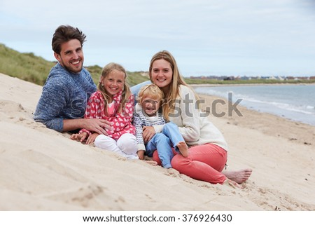 Portrait Of Family Sitting In Sand Dunes Together