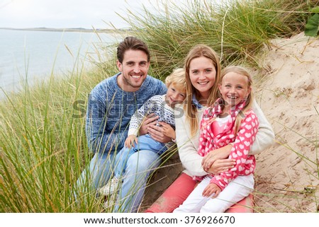 Portrait Of Family Sitting In Sand Dunes Together - stock photo