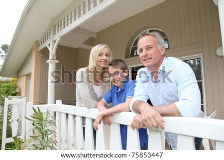 Portrait of family standing on their home terrace - stock photo
