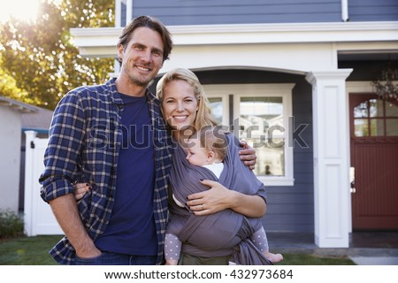Portrait Of Family Standing Outside House - stock photo