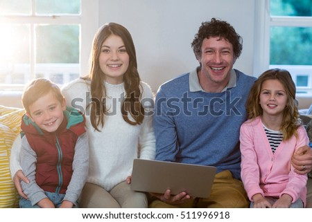 Portrait of family using laptop at home