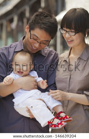 Portrait of family with baby, holding baby - stock photo