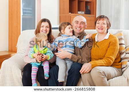 Portrait of family with grandmother on sofa in home - stock photo