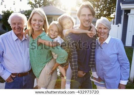 Portrait Of Family With Grandparents Standing Outside House - stock photo