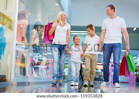 Portrait of family with paperbags walking in the mall - stock photo