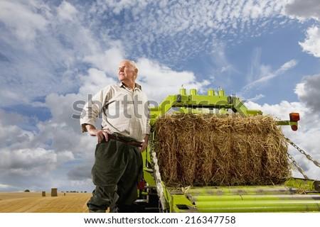 Portrait of farmer standing near machinery with straw bale - stock photo