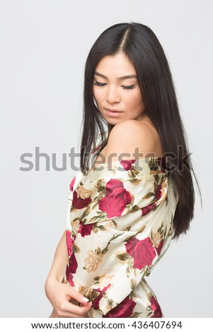 Portrait of fashion asian lady in spring dress demonstrating her shoulder to camera in studio. Beautiful brunette lady looking down. - stock photo